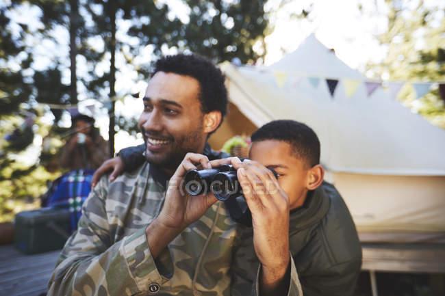Цікавий батько і син з біноклем у таборі. — стокове фото
