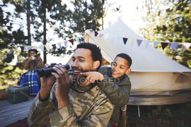 Щасливий, допитливий батько і син з біноклем у таборі. — стокове фото