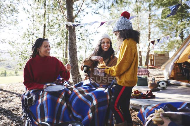 Glückliches lesbisches Paar und Tochter frühstücken auf sonnigem Campingplatz im Wald — Stockfoto