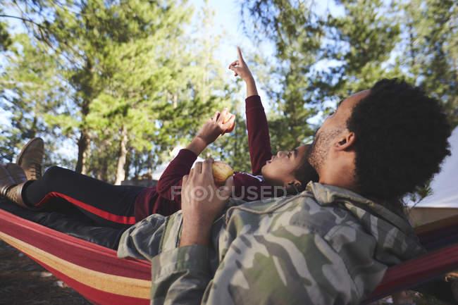 Батько з донькою відпочивають у гамаку під деревами. — стокове фото