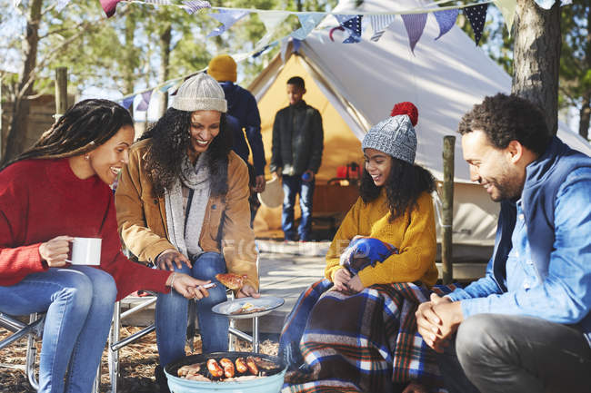 Happy friends and family cooking at campsite campfire — Stock Photo
