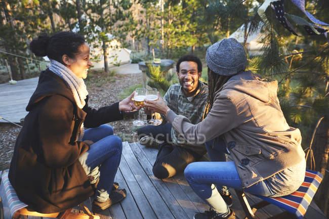 Amigos felizes bebendo vinho no acampamento na floresta — Fotografia de Stock