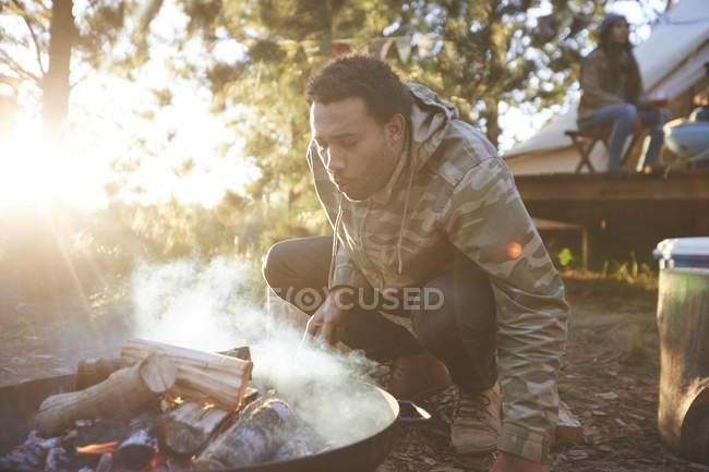 Homme soufflant sur le feu de camp dans les bois ensoleillés — Photo de stock