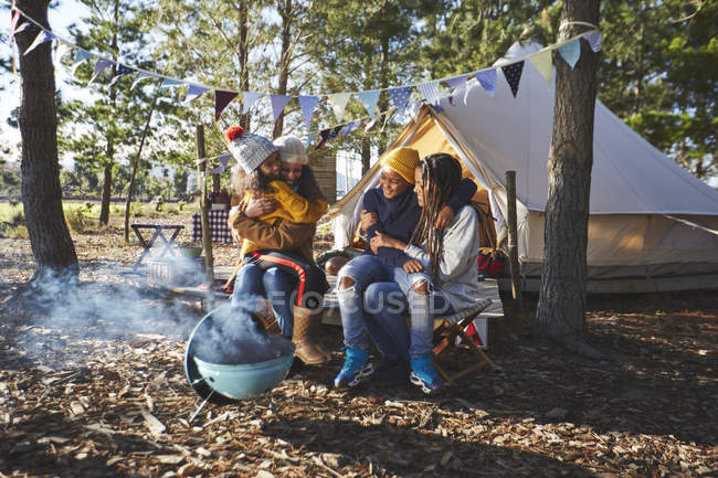Happy, affectionate lesbian couple with kids at sunny campsite — Stock Photo