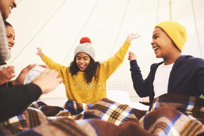 Счастливая семья играет в карты в кемпинге юрты — стоковое фото
