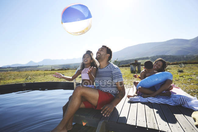 Playful family with beach ball at sunny, summer swimming pool — Stock Photo