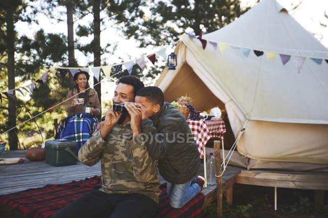 Цікавий батько і син, які використовують бінокль за межами юрти в кемпінгу. — стокове фото