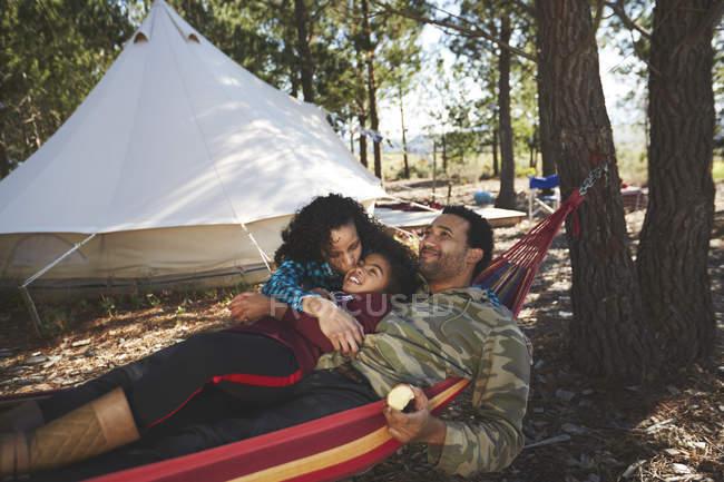 Счастливая семейная релаксация в гамаке в кемпинге в лесу — стоковое фото