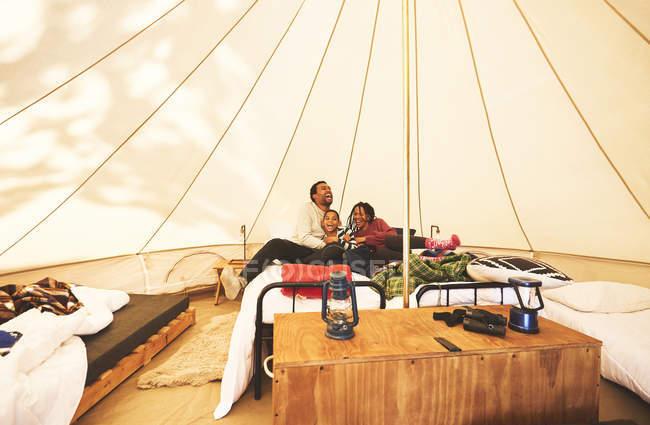 Família feliz e despreocupada relaxando na cama no acampamento yurt — Fotografia de Stock