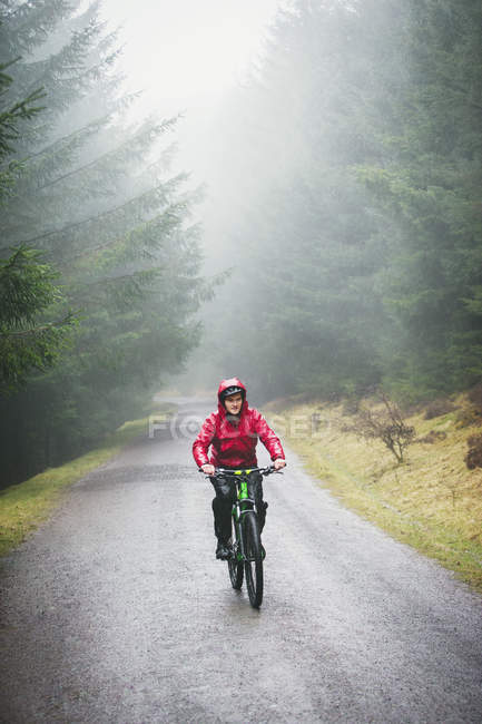 Man mountain biking in rain — Stock Photo