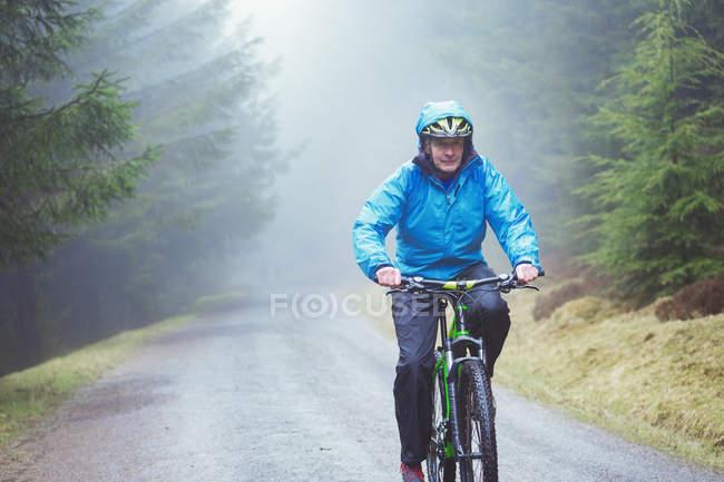 Senior man mountain biking in woods — Stock Photo
