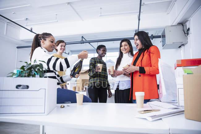 Жінки - підприємці, які святкують новий офіс з шампанським. — стокове фото