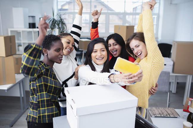Счастливые бизнесвумен переезжают в новый офис, делая селфи — стоковое фото