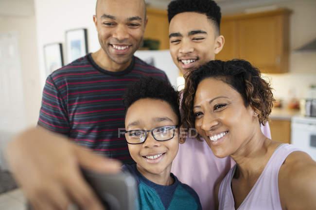 Família sorrindo tirando selfie em casa — Fotografia de Stock