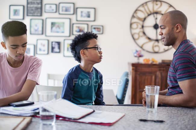 Отец и сыновья разговаривают, делают домашнее задание на кухне — стоковое фото