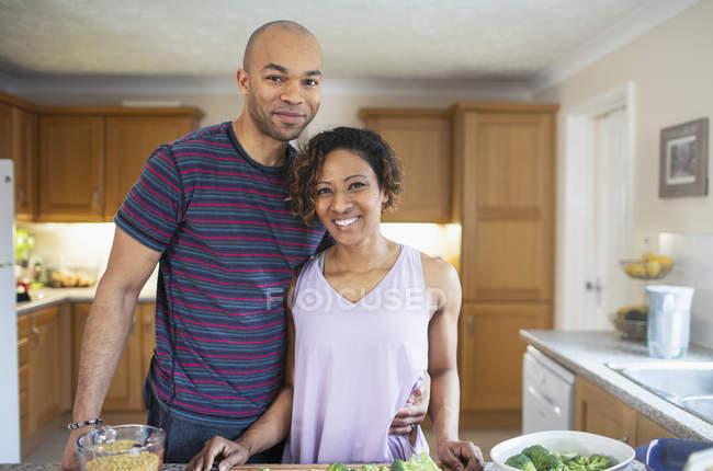 Портрет усміхаючись подружжя готує їжу на кухні — стокове фото