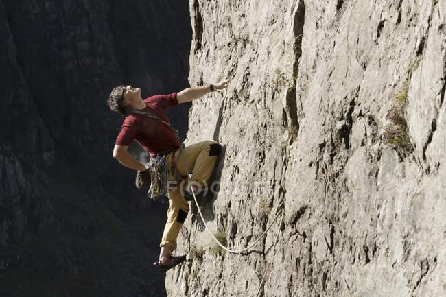 Männlicher Bergsteiger erklettert Felswand, schaut nach oben — Stockfoto
