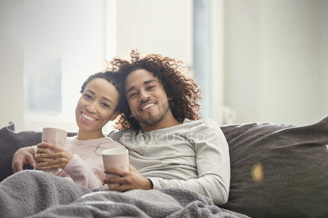 Портрет усміхається, ласкава пара відпочиває на дивані. — стокове фото