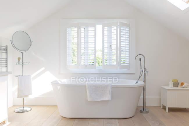 Tranquilo blanco casa escaparate baño con bañera de remojo - foto de stock