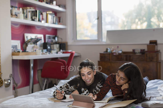 Teenage girl friends studying doing homework on bed — Stock Photo