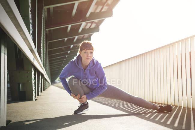 Сосредоточенная молодая бегунья, растягивающая ноги на платформе солнечного вокзала — стоковое фото