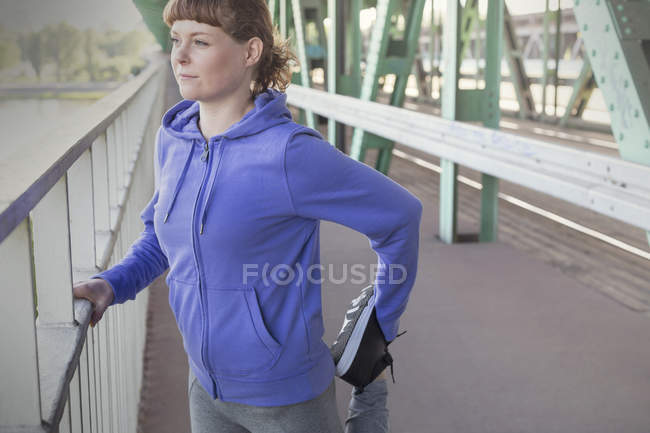 Young female runner stretching leg — Stock Photo