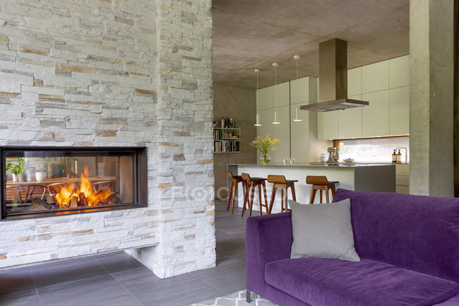Modern living room with brick fireplace open to kitchen — Stock Photo