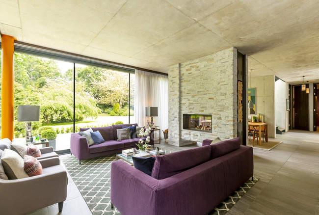 Современная гостиная с кирпичным камином и видом на сад — стоковое фото
