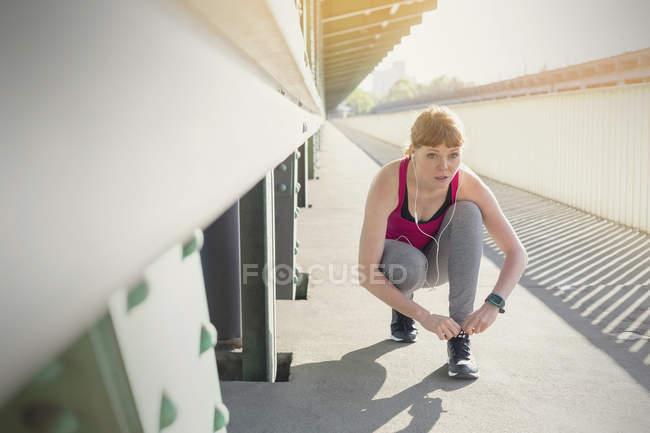 Young female runner tying shoe on sunny urban sidewalk — Stock Photo