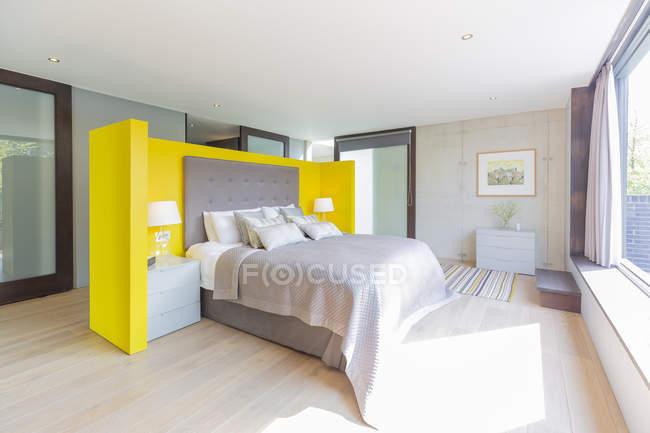 Modernes Schlafzimmer mit gelbem und grauem Kopfteil — Stockfoto