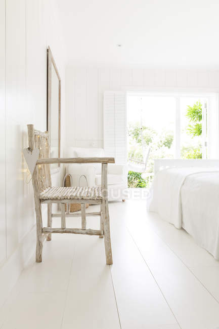 Simple wood armchair in white beach house bedroom — Stock Photo