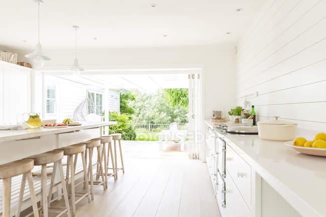 Semplice casa bianca vetrina cucina interna aperta sul patio — Foto stock