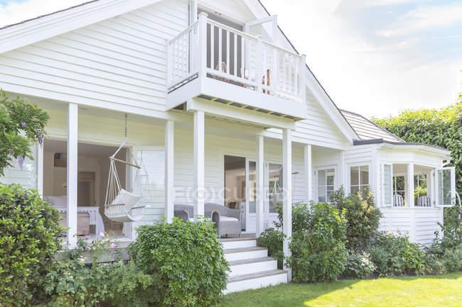 Дом с витриной и белым домом с патио и садом — стоковое фото