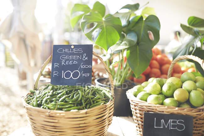Корзины свежих зеленых ознобов и лаймов на фермерском рынке — стоковое фото