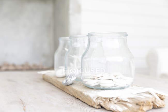 Fermer les copeaux de chocolat blanc dans un bocal sur un panneau de bois rustique — Photo de stock