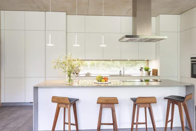 Современная белая кухня с островом и барными стойками — стоковое фото
