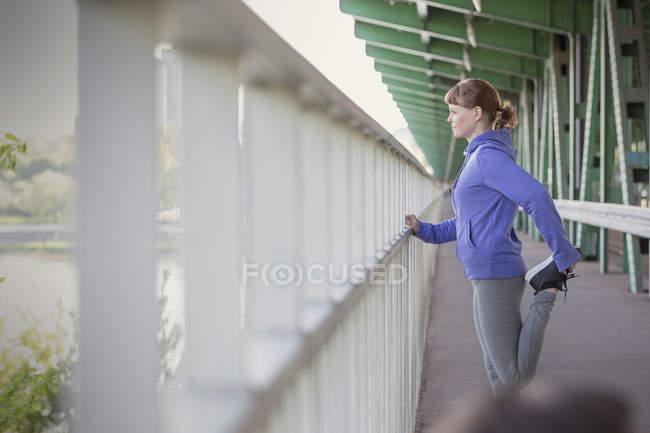 Young female runner stretching leg at urban railing — Stock Photo