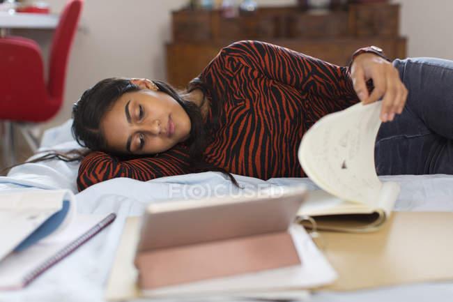 Adolescente étudiant, allongé sur le lit livre de lecture — Photo de stock