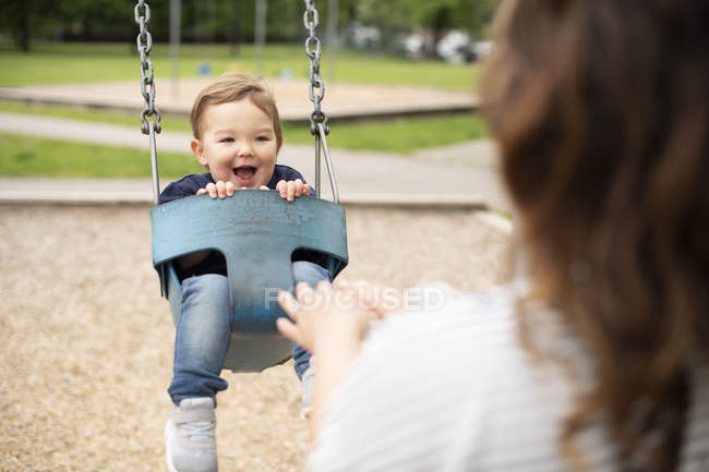 Mother pushing happy cute toddler girl in swing at playground — Stock Photo