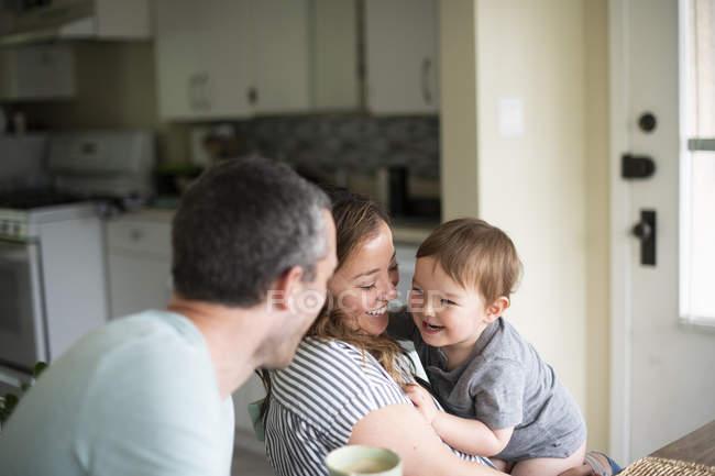 Glückliche junge Familie in der Küche — Stockfoto