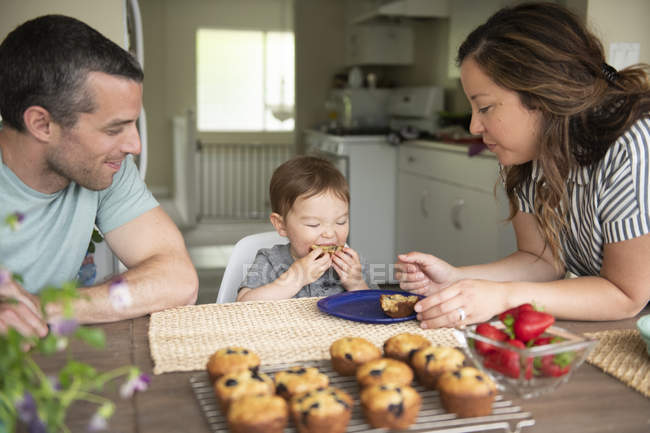 Young family eating fresh muffins in kitchen — Stock Photo