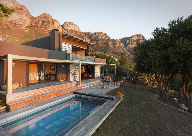 Montañas detrás de casa de lujo casa de escaparate exterior con piscina. - foto de stock