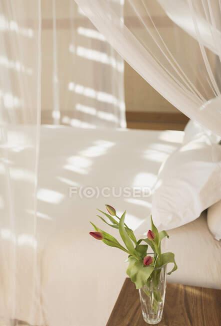 Buquê Tulipa em vaso na mesa de cabeceira ao lado de cama dossel com cortinas de gaze em tranquila moderna, casa de luxo vitrine quarto interior — Fotografia de Stock