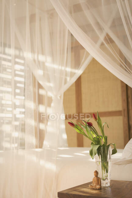 Tulip bouquet and Buddha statuette on bedside table next to canopy bed with white gauze curtains in tranquil bedroom — Stock Photo