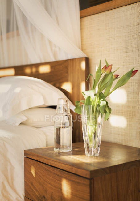Buquê de tulipa e jarro de água na mesa de cabeceira no quarto tranquilo — Fotografia de Stock