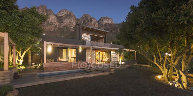 Montanhas atrás iluminado moderno, casa de luxo vitrine casa exterior à noite — Fotografia de Stock