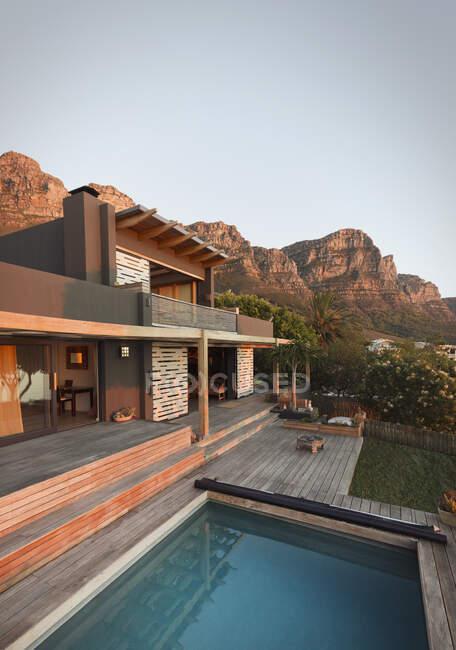 Berge hinter modernem, luxuriösem Haus präsentieren Haus im Außenbereich mit Pool — Stockfoto