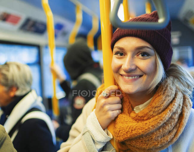 Portrait confident young woman wearing stocking cap and scarf riding bus — Stock Photo