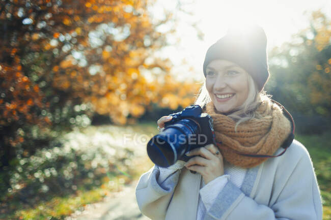 Sorridente donna con macchina fotografica digitale nel soleggiato parco autunnale — Foto stock