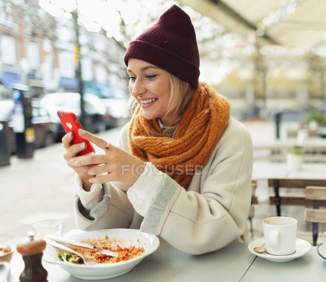 Sorrindo jovem com telefone inteligente comendo almoço no café calçada outono — Fotografia de Stock